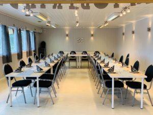 """Viser bildet av sal, med bord dekket av servietter og ballonger som det står """"50 år"""""""